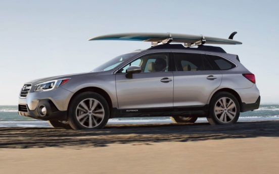 Image of a 2018 Subaru Outback parked in front of the beach.