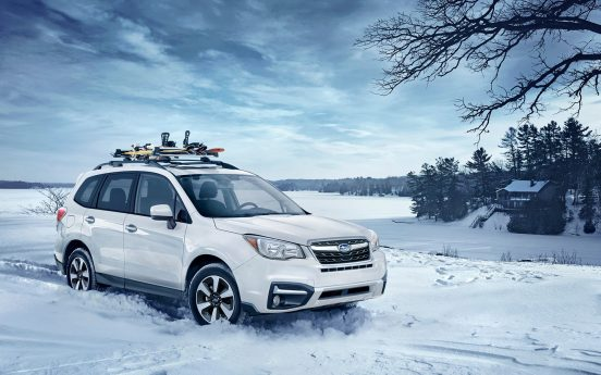 Image of a white Subaru Forester parked in a snowy countryside landscape.