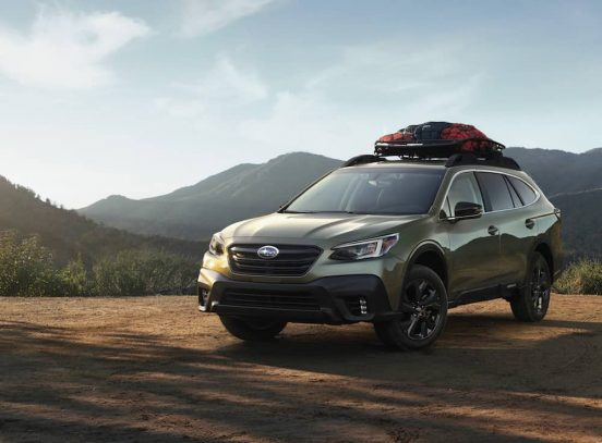 Image of a green 2020 Subaru Outback parked in a mountainous landscape.